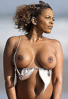 Busty Sundy Carter posing topless on a beach